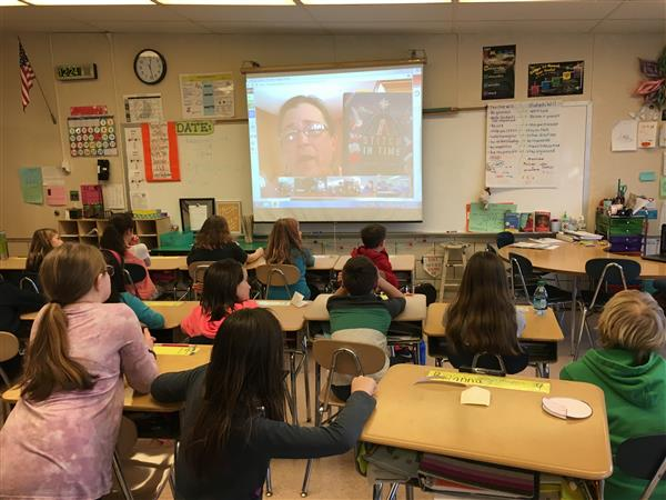 Students watch an author on Skype